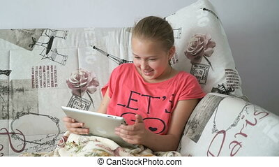 Child reading a digital tablet lying on the bed