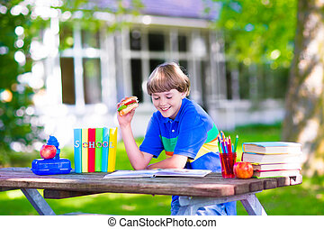 Child reading and eating sandwich at school yard