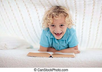 Child reading book in bed. Kids read books.