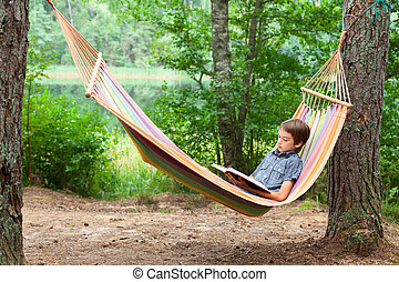 Child reading book in hammock