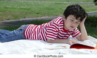 Child reading book in park