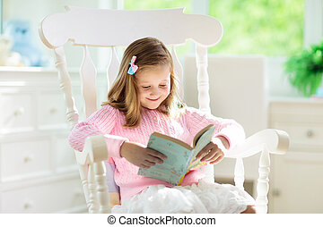 Child reading book. Kids read books. Little girl sitting on white couch in sunny living room watching pictures in story book. Kid doing homework for elementary school or kindergarten. Children study