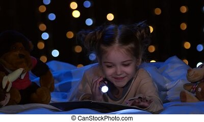 Child reads a book in the hands of a fanatic at night and she laughs. Bokeh background