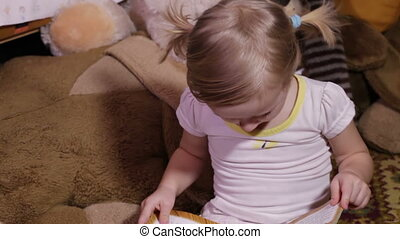 Child reads - Profile baby girl watching cartoons