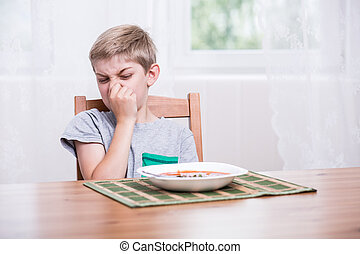 Child refusing to eat soup - Child sitting at the table and ...