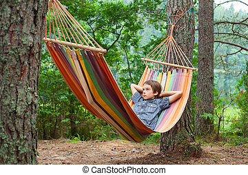 Child relaxing in hammock outdoors