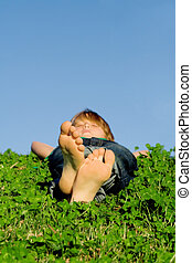 child relaxing outdoors, focus on feet.