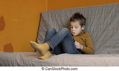 Child relaxing with tablet computer at home