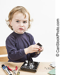 child repairing computer part. studio shot in light grey...