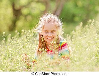Child resting on green field
