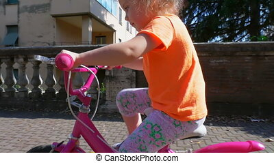 Child ride a small pink bicycle