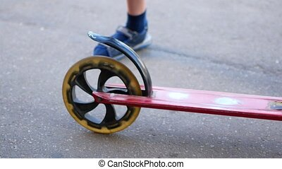 Child rides a scooter in a summer park. Carefree childhood, summer, happiness and sport activity concept