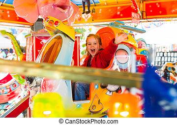 child rides on kirtag in ringelspöiel - a little girl has...