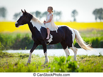 Child riding a horse in the meadow