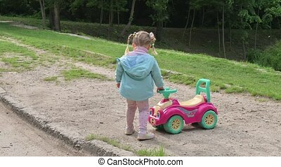 Child riding a toy car in the park