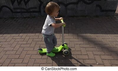Child riding green kick scooter - Child riding scooter. Kid...
