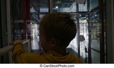 Child riding in modern glassy elevator