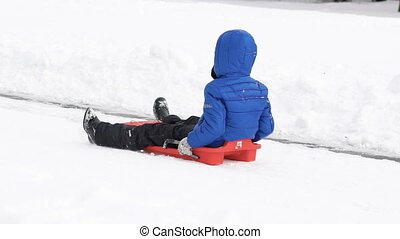 Child riding on the sled in winter park. Slowly