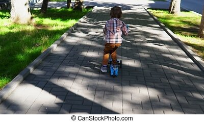 Child riding scooter on green kick board. Kid is coming from...