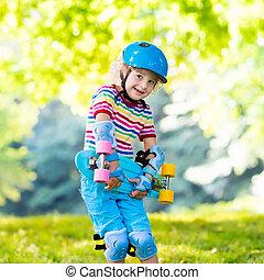 Child riding skateboard in summer park. Little boy learning...