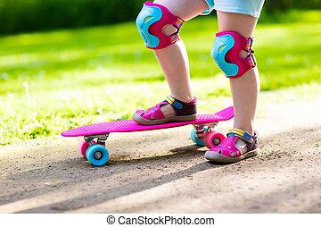 Child riding skateboard in summer park