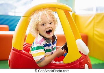 Child riding toy car. Little boy with toys.