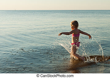 Child running into water