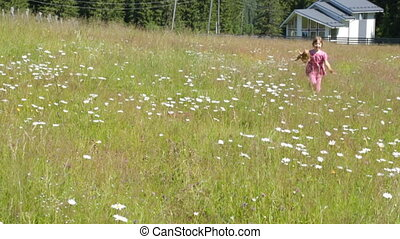 Child running through camomile field in summer morning