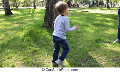 Child running with soap bubbles in the park