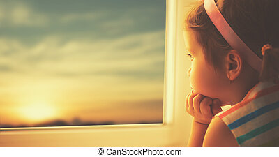 child sad little girl looking out window at sunset