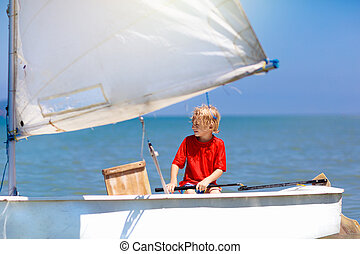 Child sailing. Kid learning to sail on sea yacht.