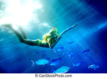 Child scuba diver with group coral fish.