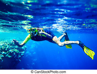 Child scuba diver with group coral fish. - Child scuba diver...