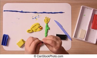 Child sculpts from plasticine hands once and crafts element naleplyaet it on the board, close-up, top view