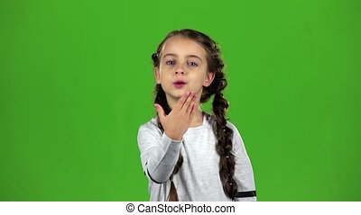 Child sends an air kiss. Green screen. Slow motion
