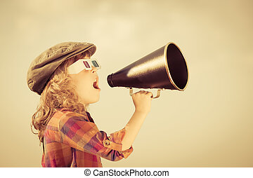 Child shouting through vintage megaphone. Cinema concept. ...