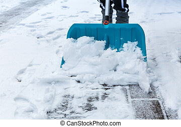Child shoveling and removing snow in front of his house in the suburb