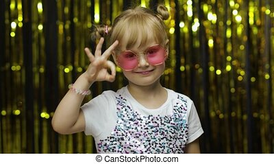Cheerful glad child showing ok gesture and smiling at camera with optimistic satisfied expression, okay sign of approval. Little fun blonde kid teen teenager girl 4-5 years old in pink sunglasses
