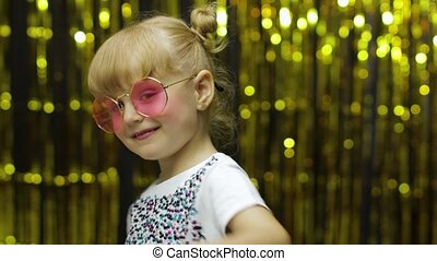 Child show thumbs up. Smiling and looking at camera. Demonstrating approval, satisfied with excellent result. Little fun blonde kid teen girl 5 years old in pink sunglasses posing on shiny background