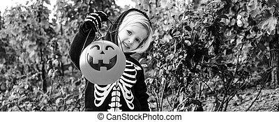 child showing Halloween pumpkin Jack O'Lantern basket