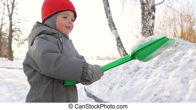 Child shows snow green shovel - Child gray jumpsuit shows...