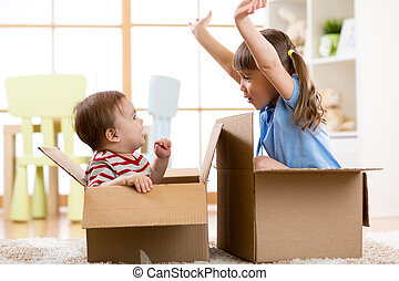 Child sister and toddler brother playing in cardboard boxes