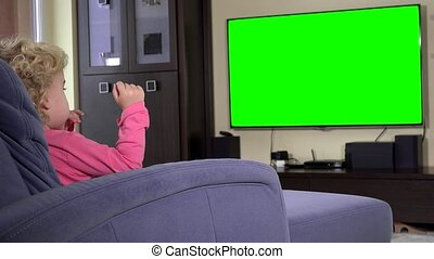 child sit in front of a tv and watch a children show on. Green chroma key screen