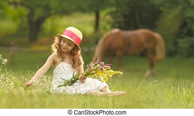 Child sits in a clearing, turns over the torn wild flowers and makes a bouquet from them. Slow motion