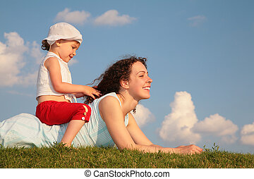 Child sits on back of mother lying on grass