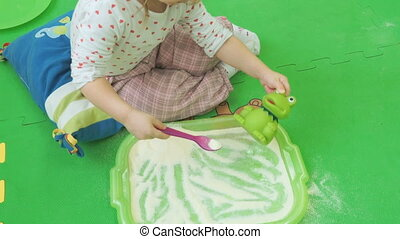 Child sits on floor and plays with a toy
