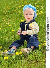 child sits on grass