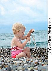 child sits on pebble beach