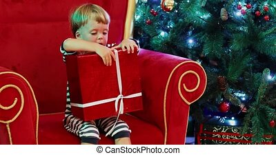 Baby boy at Christmas tree with gift