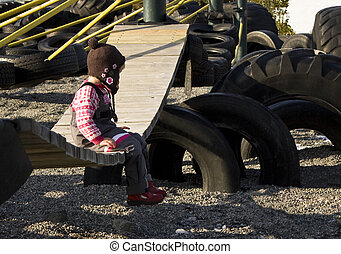 Child sitting alone on a playground swing.